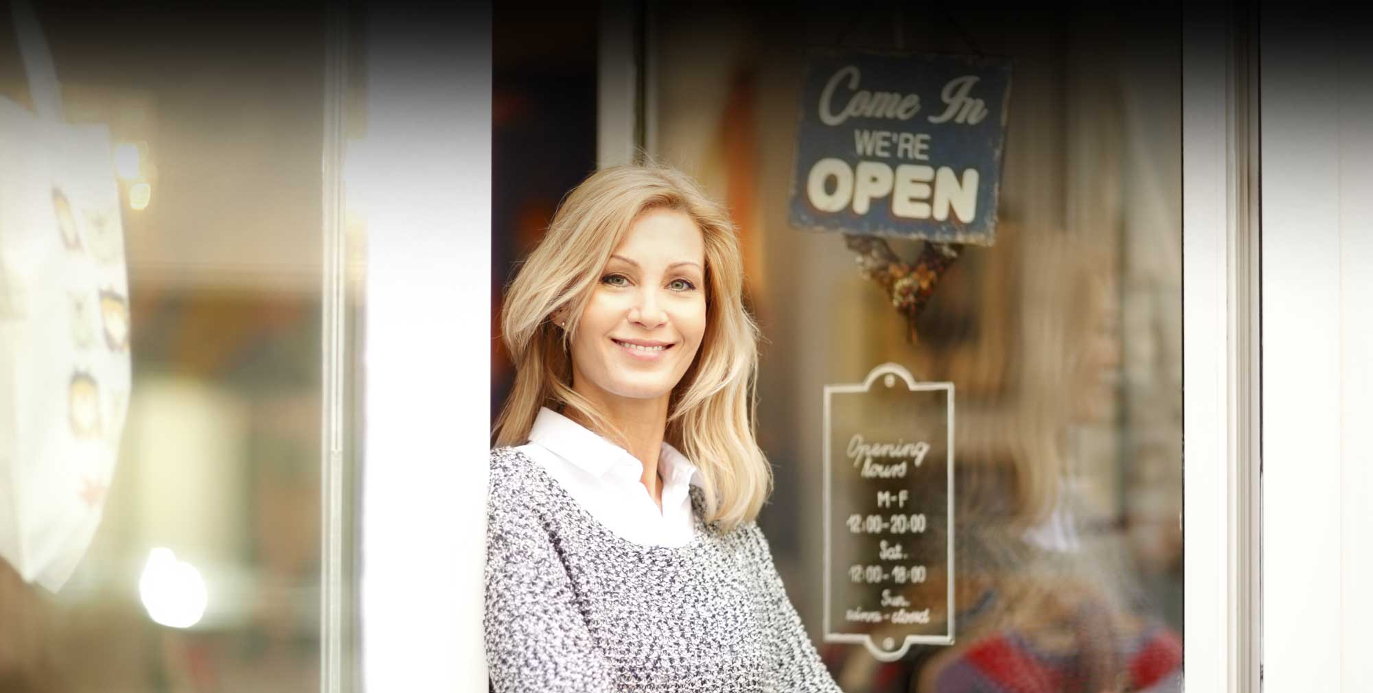 A smiling woman standing in the doorway of her local business.